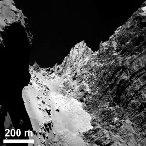 """Diese Aufnahme zeigt den Einschnitt zwischen den beiden Kometenköpfen. Die Klippe rechts im Bild tauften die Forscher """"Hathor"""", das schmale Tal """"Hapi"""". Beachte die Maßangabe. (#08)"""