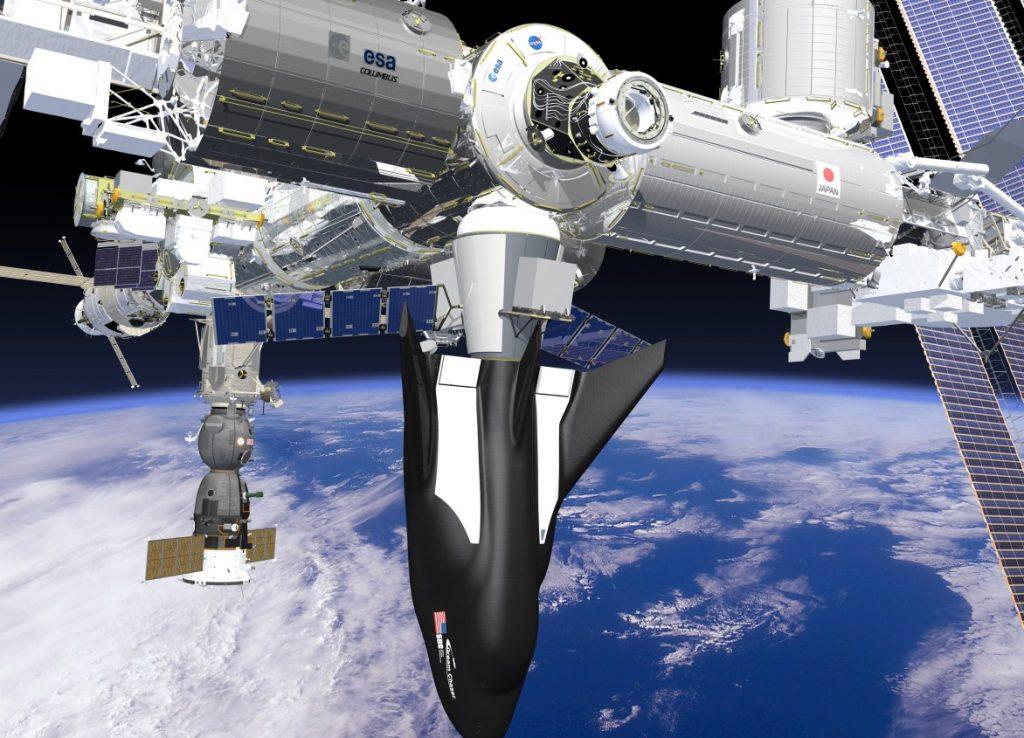 """Hier hat ein """"Dream Chaser"""" an der Internationalen Raumstation ISS angedockt. Am Heck ist das Lade- und Schleusenmodul zu erkennen, das wahrscheinlich in Europa produziert werden wird. Direkt hinter der Raumfähre befindet sich ein """"Sojus""""-Raumschiff. (#3)"""