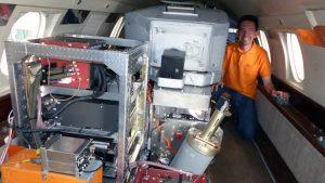 """DLR-Wissenschaftler Oliver Reitebuch in der Kabine der """"Falcon"""" 20 mit dem """"Aladin""""-Lidar – das ist der schräg eingebaute Zylinder im Vordergrund. (#6)"""