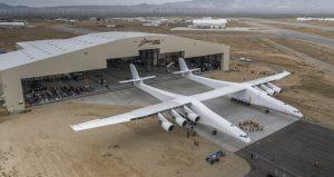 Die Spannweite des Doppelrumpf-Flugzeugs beträgt 117 Meter. Unter dem Mittelflügel wird es Raketen zu ihrer Startposition in großer Höhe tragen.  (#2)