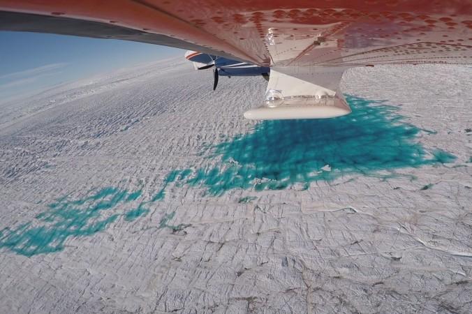 Das AWI-Forschungsflugzeug Polar 6 bei der ersten Messkampagne des Ultra-Breitband-Eisradars, dessen Antennen unter dem Rumpf und den Flügeln montiert sind. Auf dieser Aufnahme fliegt das Flugzeug über den 79-Grad-Nordgletscher in Grönland. Deutlich zu erkennen sind die Schmelzwasserseen auf der Gletscheroberfläche. (#6)