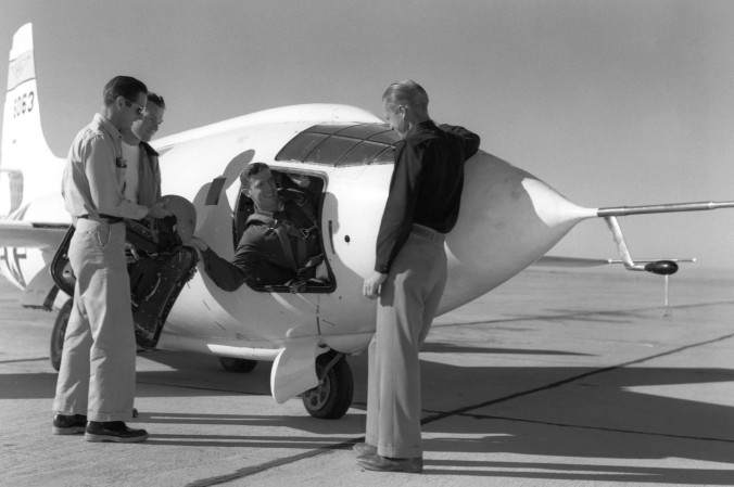 Aufgenommen ca. 1950: Nach der geglückten Landung gibt Testpilot John Griffith dem Mechaniker Dick Payne seine Ausrüstung, während zwei andere Angehörige des Wartungsteams, Ed Edwards und Clyde Bailey, dabei stehen. (#5)
