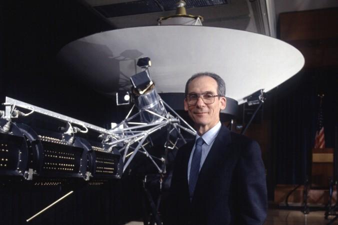 """Edward Stone vor einem Modell der """"Voyager""""-Sonde. Er ist Physiker und Planetenforscher. Stone arbeitete seit 1961 in der Weltraumforschung und stieß 1972 als Projekt-Wissenschaftler zum """"Voyager""""-Team. Er wurde dessen Sprecher und leitete zwischen 1991 und 2001 das Jet Propulsion Laboratory der NASA, dass auch die """"Voyager""""-Missionen betreut. (#4)"""