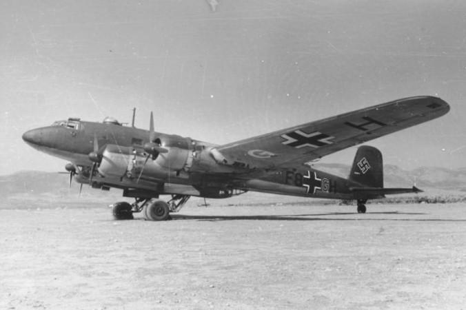 """Aufnahme von 1941 der Focke-Wulf 200 C-3 """"Condor"""" F8+GH auf einem Feldflugplatz im Mittelmeerraum. Die Kennung F8+.. zeigt, dass das Flugzeug zum KG 40 gehört. Militärische Ausrüstung wie Bombengehänge, die Bodenwanne unter dem Rumpf und Waffentürme sind deutlich zu erkennen. Typisch für eine C-3 ist der vordere Drehturm mit einem 13mm-MG 131. (#3)"""