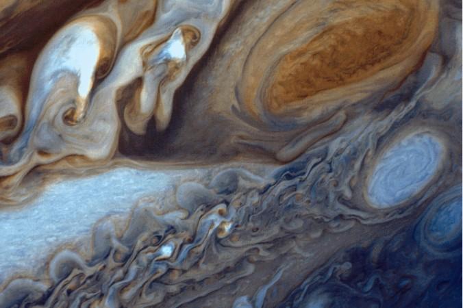 """""""Voyager"""" lieferte dieses Bild von Jupiters Rotem Fleck und den umgebenden Wolkenwirbeln. Der Rote Fleck ist ein stationärer Wirbelsturm, der bereits den frühen Astronomen auffiel. Die Erde passt gleich mehrfach hinein. (#5)"""