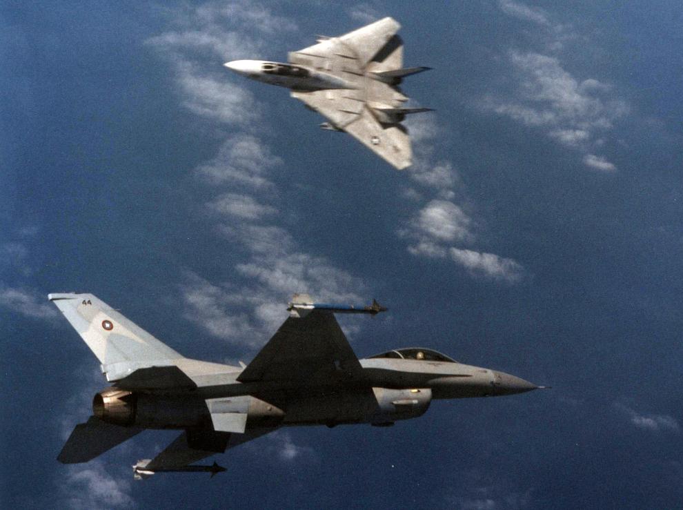 """Mit der General Dynamics F-16N, einer F-16-Version ohne Bewaffnung, simulierte die U.S. Navy sowjetische Jäger wie die damals neue MiG-29 Fulcrum. Hier eine F-16N (vorne) im Luftkampf mit einer F-14A """"Tomcat"""". (#8)"""
