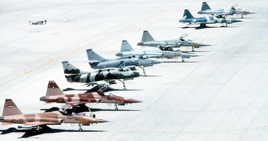 """Aufgenommen 1993: Auf dem Hallenvorfeld der NAS Fallon in Nevada stehen 'adversary'-Maschinen verschiedener Typen: (von vorne) Zwei Northrop F-5E """"Tiger II"""", zwei Douglas A-4M """"Skyhawk"""", eine zweisitzige F-5F """"Tiger II"""" und drei einsitzige F-5E. (#1)"""