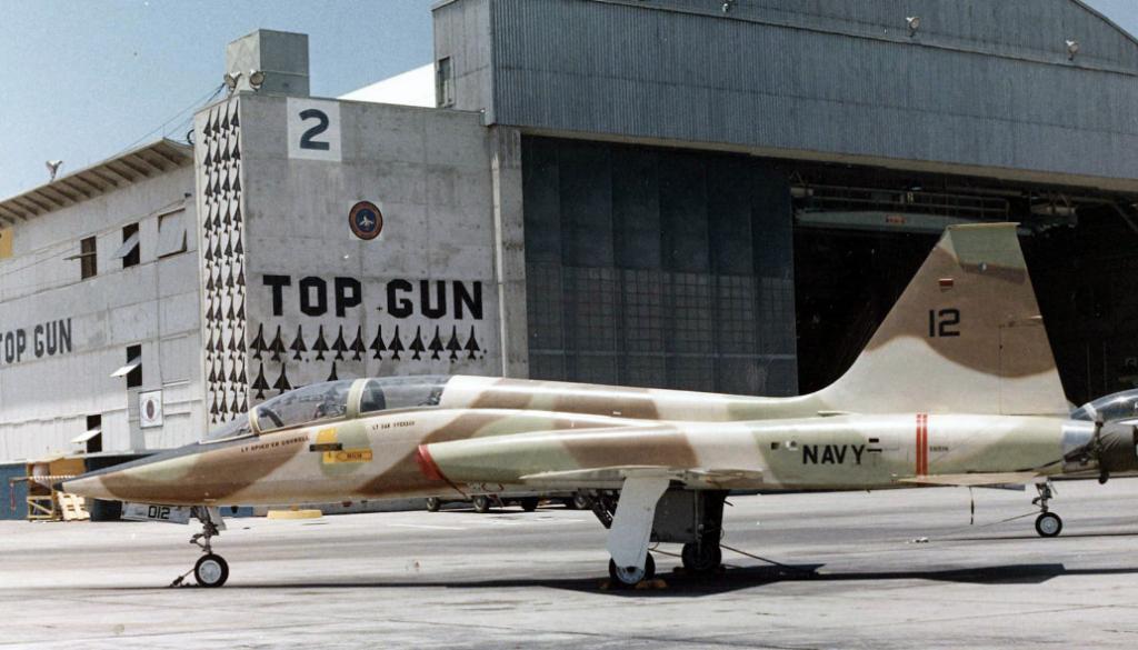 """In den Anfangsjahren nutzte die """"Top Gun""""-Schule zweisitzige Überschalltrainer vom Typ Northrop DT-38 """"Talon"""" zur Feinddarstellung. Diese """"Talon"""" wurde 1974 in Miramar aufgenommen. Später trat die verbesserte Northrop F-5 """"Tiger II"""" an die Stelle der DT-38.  Die MiG-Silhouetten auf dem Hangar sollen über Vietnam abgeschossene Feindmaschinen darstellen. (#3)"""