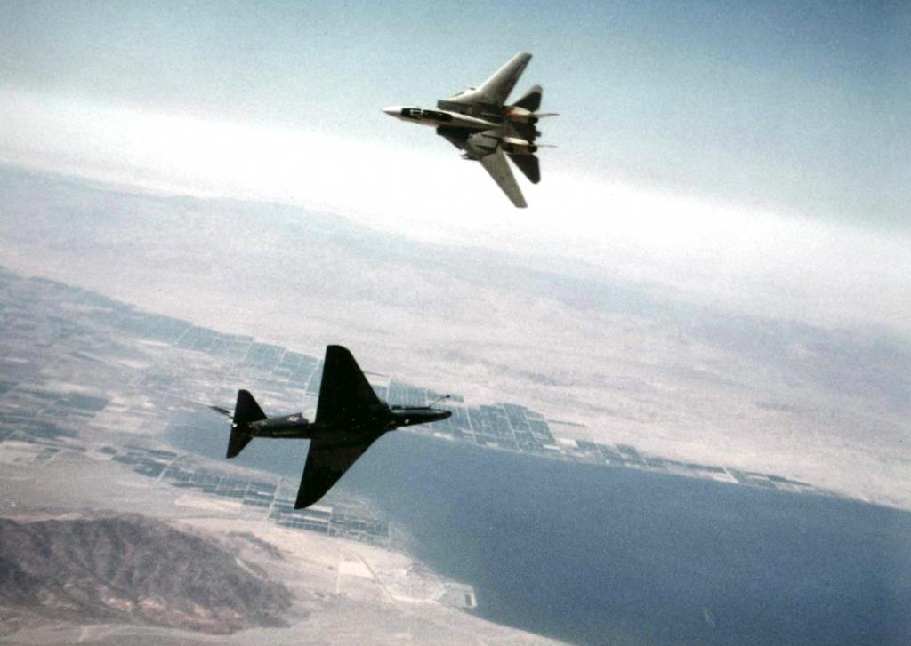 """Auf diesem Bild von 1982 duellieren sich eine 'adversary'-Maschine vom Typ Douglas A-4F """"Skyhawk"""" und eine Grumman F-14A """"Tomcat"""". Im Hintergrund die Salton Sea, ein Salzsee in Kalifornien. (#7)"""